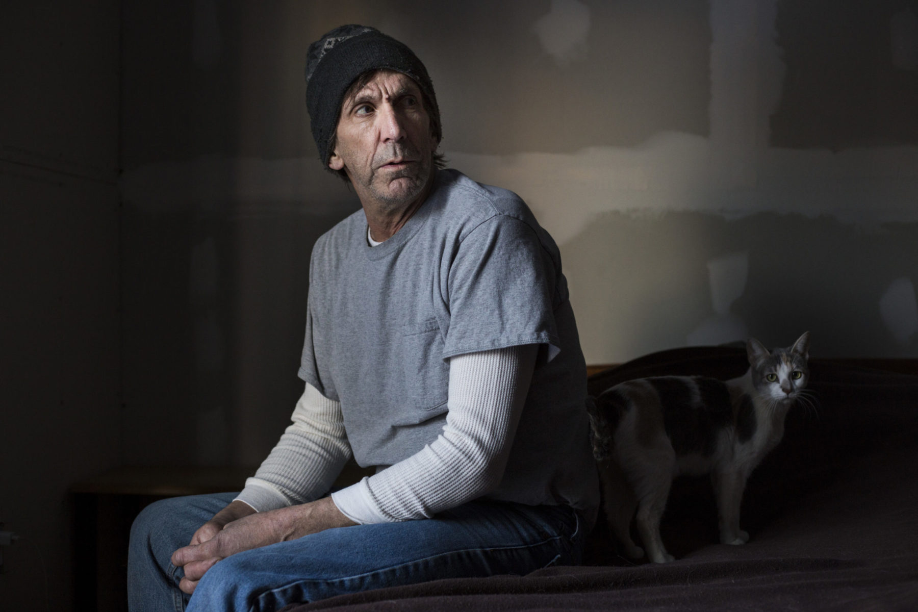 Tim Monahan, 58, sits in his bedroom at his home