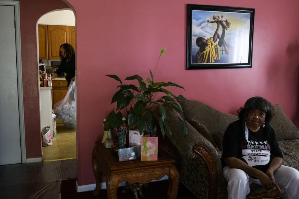 An older Black woman sits on a brown couch in a pink room. Another Black woman is visible through a doorway cleaning the kitchen while holding a large clear trash bag filled with empty water bottles.